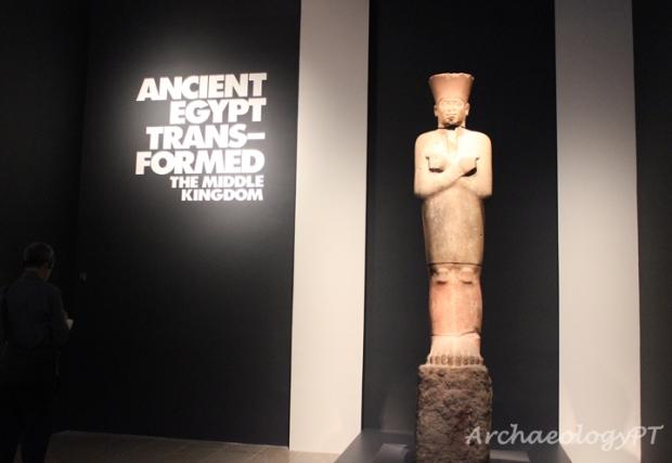 「古埃及轉化:中王國時期」展場入口,孟圖霍特普二世穿著慶典服飾像(上色砂岩,2030-2000 B.C.,底比斯出土,紐約大都會博物館藏)。